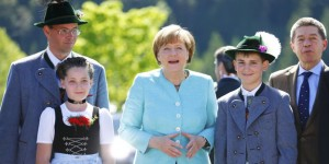 German Chancellor Merkel and her husband Sauer are welcomed by local residents in Kruen