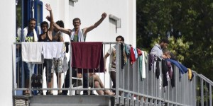 Migrants wave as they stand on the staircase of an asylum seekers accomodation facility in the eastern German town of Heidenau