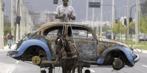 File photo of a Brazilian man transporting on his horse-drawn cart the remains of a Volkswagen Beetle that caught fire and was abandoned by its owner in Rio de Janeiro