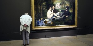 "A visitor looks at "" Le dejeuner sur l'herbe "" (Luncheon on the Grass) by Edouard Manet exhibited at the Orsay Museum in Paris"