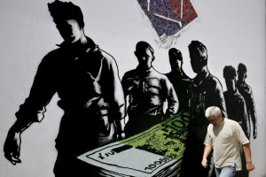"""File photo of a man making his way past graffiti """"Death of euros"""" made by French street artist Goin in Athens"""